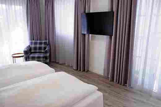 Großes Schlafzimmer mit Fenster und Balkontüren in der Ferienwohnung Gams im Bayerischen Hof und den Löwen Suites