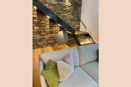 Sofa und Treppenaufgang im Penthouse Nr. 9, Ferienwohnung im Bayerischen Hof in Oberstaufen